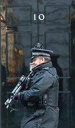 © Licensed to London News Pictures. 18/11/2014. Westminster, UK . A police officer with an automatic rifle infant of Number 10. Ministers and MP's on Downing Street 18th November 2014. Photo credit : Stephen Simpson/LNP