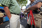 elderly couple standing and waiting at an outdoors farmers market