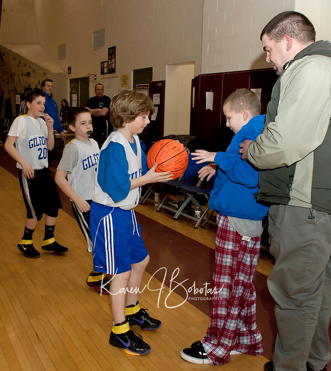 Dominick Troiano presents 5th grader Joseph Sawyer along with his dad Peter Sawyer a game ball signed by his team mates during the 18th annual Francouer Babcock Basketball Tournament Friday evening.  Joseph is recovering from brain tumor surgery and an honorary member of the Gilford Senior Boys team.  (Karen Bobotas/for the Laconia Daily Sun)