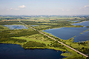 Nederland, Noord-Holland, Naarden, 14-07-2008; natuurgebied Naardermeer, oudste en een van de bekenste natuurreservaten van Nederland, bezit van de Vereniging voor Natuurmonumenten (grondlegger Jac. P. Thijsse); natuurreservaat, gezien naar het Westen (Weesp), bebouwing Amsterdam aan de horizon); .momenteel wordt het gebied uitsluitend doorsneden door de spoorlijn Weesp - Naarden/Bussum, er zijn echter plannen om een nieuwe weg aan te leggen vlak langs en onder het gebied, namelijk tussen het nabij gelegen Almere en Amstelveen (en door naar Schiphol) dit in verband met de fileproblematiek rond de hoofdstad; Rijkswaterstaat overweegt echter de Gaasperdammerweg te verbreden ivm die files en zo het Naardermeer te sparen; . .luchtfoto (toeslag); aerial photo (additional fee required); .foto Siebe Swart / photo Siebe Swart
