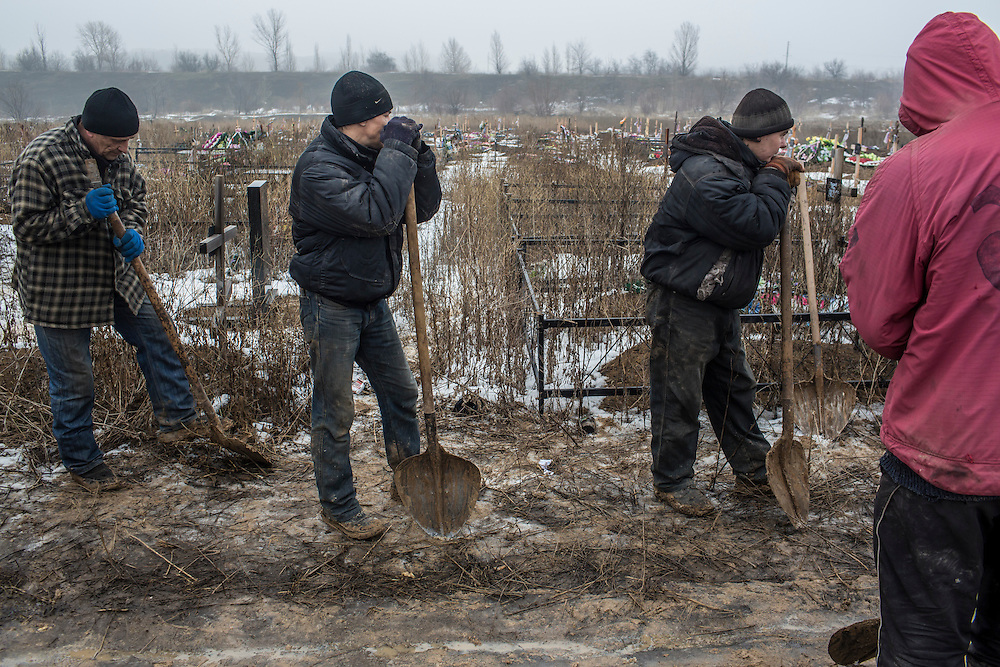 DONETSK, UKRAINE - JANUARY 30, 2015: Gravediggers pause after the funeral of Anatoliy Bogdan, 54, who was killed by shelling, at Yuzhnaya Cemetery on January 27 in Donetsk, Ukraine. At least seven people were killed in two shelling incidents in Donetsk today, the deadliest day for civilians in more than a week, as peace talks in the Belarussian capital of Minsk were postponed. CREDIT: Brendan Hoffman for The New York Times