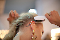 A model brushes her hair done backstage for the Brazilian brand, Osklen, at São Paulo Fashion Week for Summer Season 2013/2014, at Bienal, in Ibirapuera Park, São Paulo, Brazil, on Thursday, March 21, 2013.