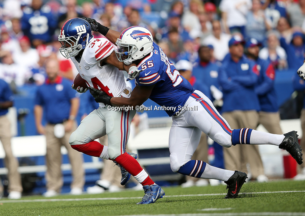 New York Giants running back Shane Vereen (34) is tackled by Buffalo Bills defensive end Jerry Hughes (55) as he runs the ball in the third quarter during the 2015 NFL week 4 regular season football game against the Buffalo Bills on Sunday, Oct. 4, 2015 in Orchard Park, N.Y. The Giants won the game 24-10. (©Paul Anthony Spinelli)
