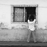 Man standong on a sidewalk looking in to a house through a window in Nahuízalco, El Salvador