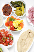 A table set with local salads such as eggplant, olives, Hummus, green salad and hot peppers usually served with pita as a mezze in middle eastern restaurants in Israel