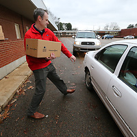 Kevin Warren helps load cars with boxes of food at the Baldwyn School District Food Pantry.