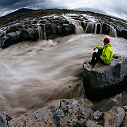 Gavriel Jecan looks down at the fast flowing rapids of a fork in the Hvítá River.