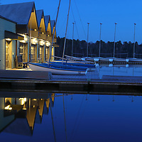 The Butler boathouse at Wellesley College on a beautiful spring night. The beautifully lit Lake Waban boathouse with its sailboats was beautifully reflecting in the quiet water of Lake Waban at the blue hour. This boathouse supports Wellesley athletics and recreational programs and is home to the crew team and sailing team. It provides recreational access to the lake for students. Wellesley College is a private, women's, liberal-arts college located in the town of Wellesley, Massachusetts. It is ranked the third best liberal arts college in the United States. Notable alumnae include Hillary Clinton, Madeleine Albright, Soong Mei-ling, Cokie Roberts, and Diane Sawyer. <br />