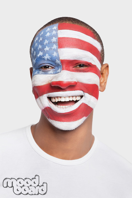 Portrait of happy young Hispanic man with North American flag painted on face against white background