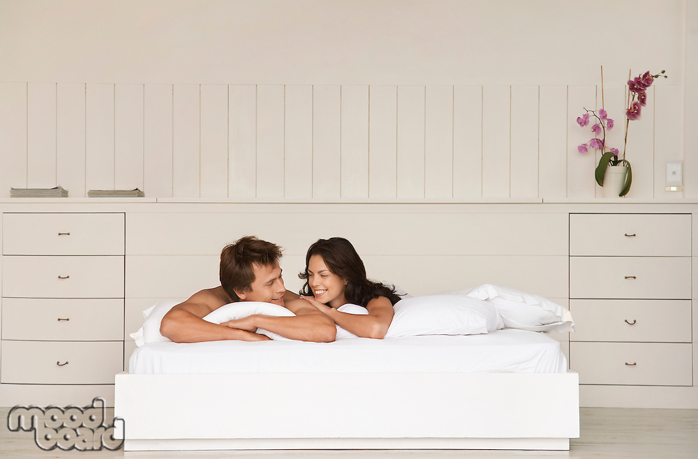 Couple lying in bed head and shoulders in bedroom