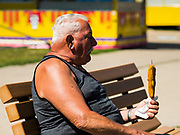 30 JULY 2019 - DES MOINES, IOWA:  A man looks at the corn dog he just bought at the Westmoreland Concessions corn dog booth on the Iowa State Fair fairgrounds. The Iowa State Fair Is one of the largest state fairs in the United States and runs for 10 days. In 2019, it runs from August 8 to 18. More than one million people attend the fair every year. Most of the food concessions at the fair don't open until August 3, when exhibitors arrive, but the Westmoreland Concessions corn dog stand opened on July 28. One of the stand's workers said a lot of people drive out to the fairgrounds the week before the fair to buy corn dogs because the fair is so crowded and concession lines are very long.    PHOTO BY JACK KURTZ