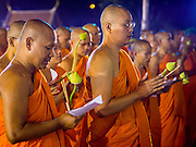 "04 MARCH 2015 - BANGKOK, THAILAND:  Buddhist monks pray in front of the ""wiharn,"" or prayer hall, at Wat Benchamabophit on Makha Bucha Day. Makha Bucha Day is an important Buddhist holy day and public holiday in Thailand, Cambodia, Laos, and Myanmar. Many people go to temples to perform merit-making activities on Makha Bucha Day. Wat Benchamabophit is one of the most popular Buddhist temples in Bangkok.   PHOTO BY JACK KURTZ"