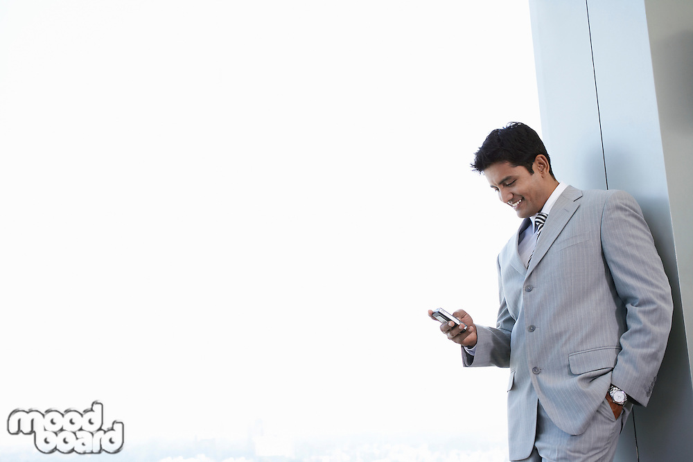 Happy young businessman reading text message on cell phone at office