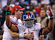 New York Giants quarterback Eli Manning jumps onto defensive end Justin Tuck after defeating the New England Patriots in the NFL Super Bowl XLVI football game in Indianapolis, Indiana, February 5, 2012. REUTERS/Jim Young