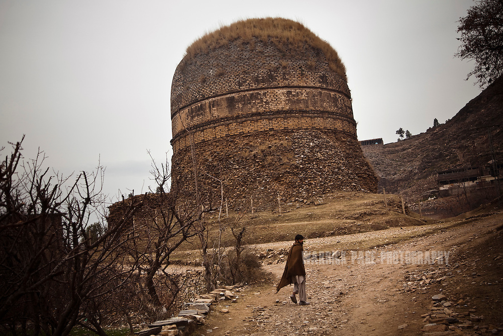 A local villager walks past the Shingardar Stupa in the Swat Valley, on February 11, 2011, in Gumbatuna, Pakistan. The Kingdom of Gandhara lasted from early 1st millennium BC to the 11th century AD, and was located in northern Pakistan and eastern Afghanistan. (Photo by Warrick Page)