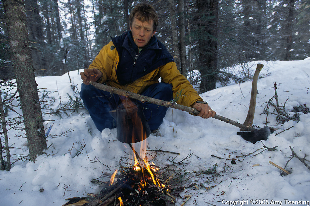 HAINES JUNCTION, BC- FEBRUARY 22: Trapper Lance Goodwin stops on his trapline to build a fire to heat water for tea February 22, 2005 in Haines Junction, British Columbia. Goodwin says each morning's tracks through the snow is like reading a daily newspaper with last night's story of the forest. In 1999 the Colorado Division of Wildlife (CDOW) began a lynx reintroduction program, trapping the animals in Canada and bringing them to Colorado. The goal is to re-establish the lynx population in the state, which has been nonexistent since the 1970s, to a viable level where the population that can sustain itself. The program has brought in 204 lynx between 1999 and 2005. There have been 71 known deaths, and 101 kittens born. The program is considered widely as a success, however the program has also instigated controversy protests from animal rights groups and developers. (Photo by Amy Toensing). _________________________________<br />