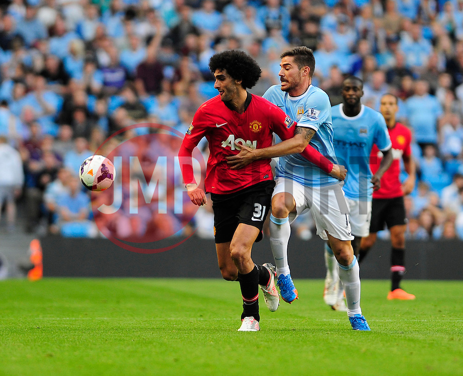 Manchester City's Javi Garcia and Manchester United's Marouane Fellaini jostle for the ball  - Photo mandatory by-line: Dougie Allward/JMP - Tel: Mobile: 07966 386802 22/09/2013 - SPORT - FOOTBALL - City of Manchester Stadium - Manchester - Manchester City V Manchester United - Barclays Premier League