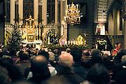 Nederland, Millingen, 10-12-2004..Kerkgangers, gelovigen, kerkbezoek, ontkerking, teloorgang, chtistendom, mis, ouderen. religie, geloof, godsdienst, katholieke kerk, eucharistie viering. Priester, pastoor, parochie...Foto: Flip Franssen