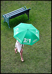 Racegoers shield from the wind and the rain on Final Day of Royal Ascot, Saturday June 23, 2012. Photo by Andrew Parsons/i-Images..All Rights Reserved ©Andrew Parsons Instructions