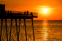 © Licensed to London News Pictures 26/06/2018. Aberystwyth, UK. People watch from the pier at sunset at Cardigan Bay in Aberystwyth at the end of a hot day when temperatures hit 28c degrees celsius in the town on the coast in North Wales. Photo credit Keith Morris/LNP