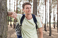 Happy young man with backpack hiking in woods