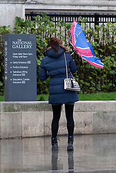 © Licensed to London News Pictures. 23/12/2013. London, UK. A tourist tries to control her umbrella outside the National Gallery in London today (23/12/2013). Weather warnings were yesterday issued for the United Kingdom predicting severe wind and rain that may affect holiday travel. Photo credit: Matt Cetti-Roberts/LNP