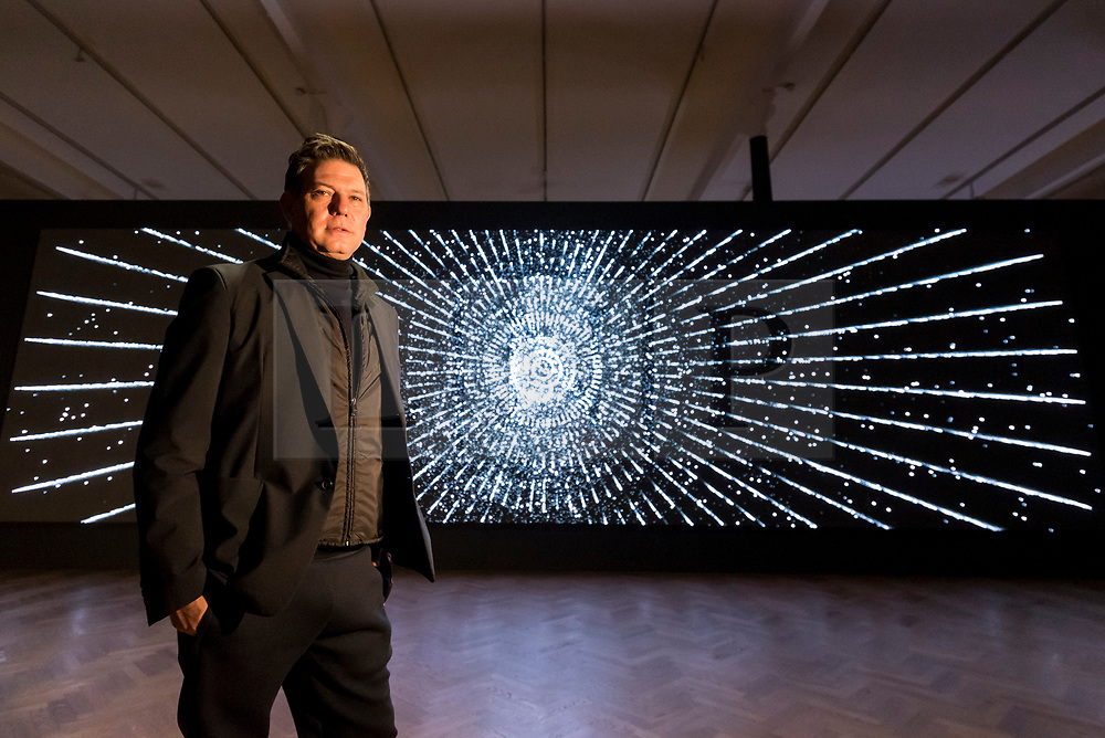 """© Licensed to London News Pictures. 21/11/2019. LONDON, UK.  American artist Leo Villareal poses by his work """"Detector"""", 2019, at a preview of his first solo exhibition at Pace gallery in Mayfair.  The works use LED lights and custom software to produce moving abstract image in a show which runs 22 November to 18 January 2020.  This exhibition coincides with the recent launch of Illuminated River, Villareal's major public artwork that will illuminate 14 bridges along the River Thames.  Photo credit: Stephen Chung/LNP"""