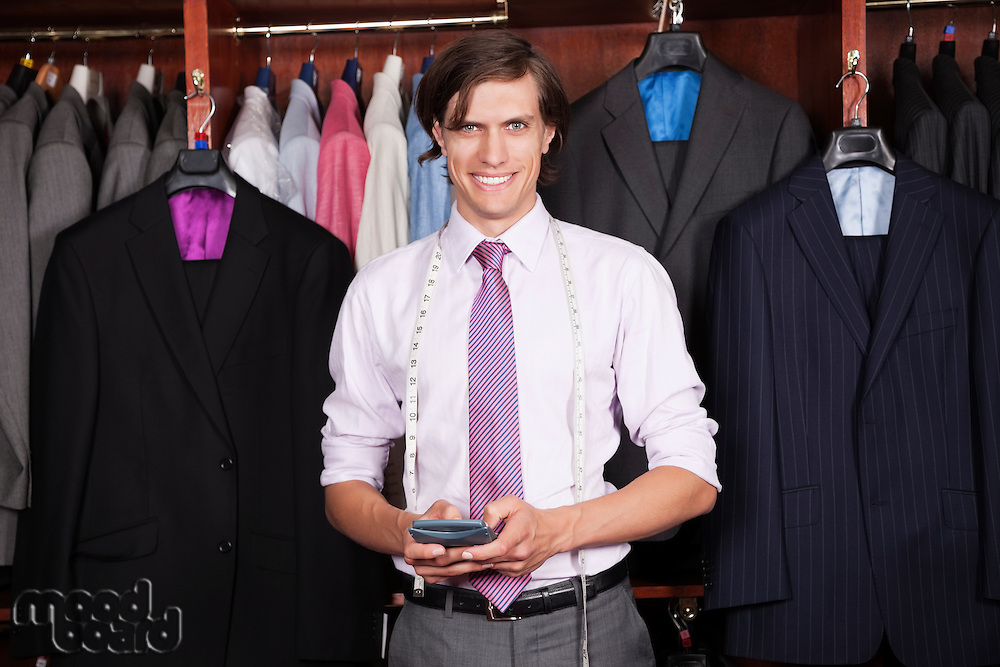 Portrait of confident man with calculator standing against display cabinet