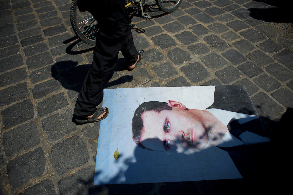 August 14, 2012 - Aleppo, Syria: A local resident passes over a picture of the president Bashar Al-Assad in Babal Nassar neighborhood in Aleppo's old city. The Syrian Army have in the past ten days increased their attacks on residential neighborhoods where Free Syria Army rebel fights have their positions in Syria's commercial capital, Aleppo.
