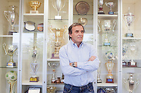SAN MARINO, SAN MARNO - 3 OCTOBER 2011: Giampaolo Mazza, 55, coach of the San Marino national team, poses in front of trofees won in the San Marino league (and not by the national team) and that are exposed at the Soccer Federation headquarters in San Marino, San Marino on October 3, 2011. Giampaolo Mazza works as a physical education teacher at the San Marino junior high-school. Non The San Marino national football team is the last team in the FIFA  World Ranking (position 203). San Marino, whose population reaches 30,000 people, has never won a game since the team was founded in 1988. They have only ever won one game, beating Liechtenstein 1–0 in a friendly match on 28 April 2004. The Republic of San Marino, an enclave surronded by Italy situated on the eastern side of the Apennine Moutanins, is the oldest consitutional republic of the world<br /> <br /> <br /> ph. Gianni Cipriano