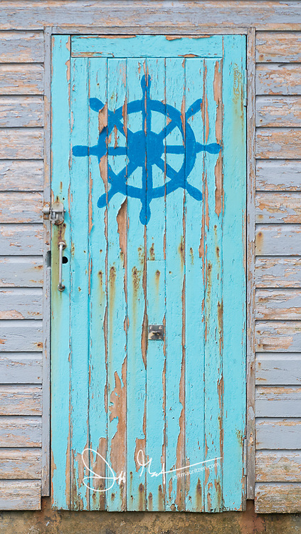 A blue door painted with a ships wheel on it.