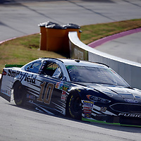 Aric Almirola (10) races through turn three to practice  for the First Data 500 at Martinsville Speedway in Martinsville, Virginia.