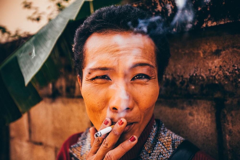 Neung, a middle-aged ladyboy in Phrae, Thailand, smokes a cigarette in a small alleyway. Neung's left eye is bruised from a fight with her boyfriend.