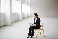 Business woman works on laptop in empty warehouse