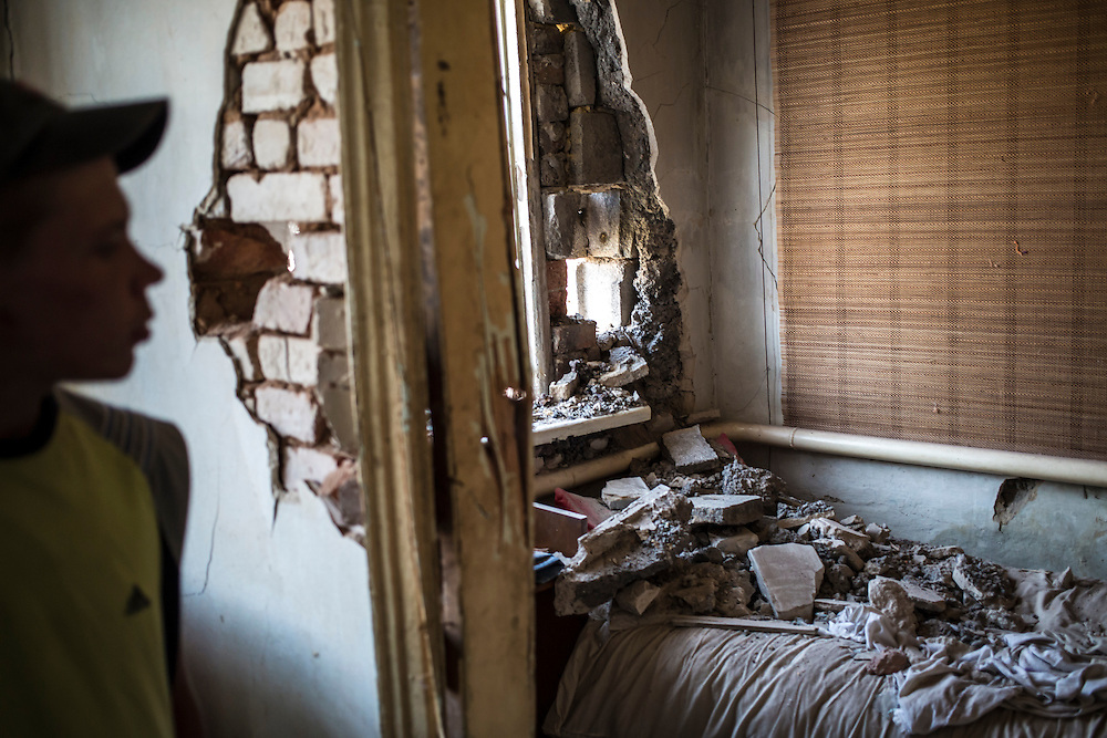 A boy looks at the damage to his friend's house caused by a shell which hit the house across the street in the Oktyabrskaya neighborhood on Sunday, July 27, 2014 in Donetsk, Ukraine.