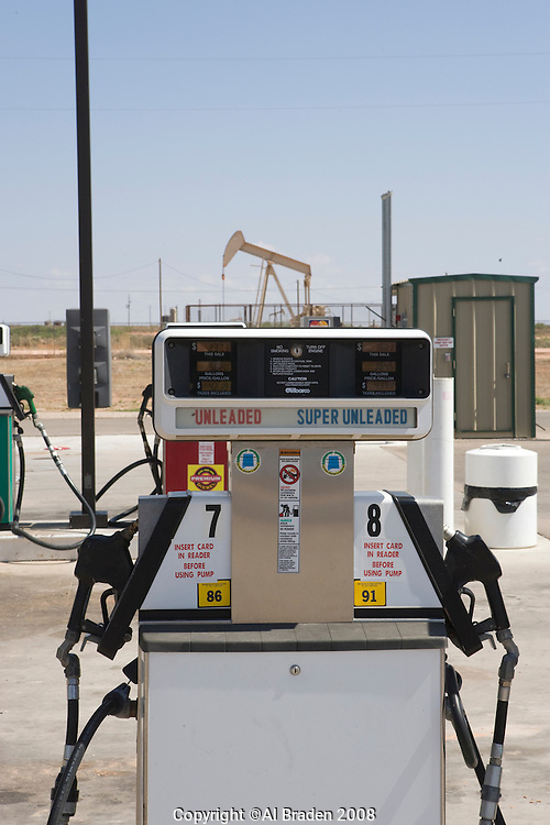 Juxtapolition of oil wells behind gasoline and diesel fuel pumps in Loco Hills NM.