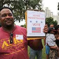 A person tries to register voters at Lake Eola park during the Orlando Is Ferguson event in downtown Orlando, Florida on Saturday, August 16, 2014. In light of the recent killing of eighteen year old Mike Brown in Ferguson, Missouri, and the aftermath, citizens are uniting to discuss possible solutions to law enforcement reform and other options for safer police and citizen encounters.  (AP Photo/Alex Menendez)