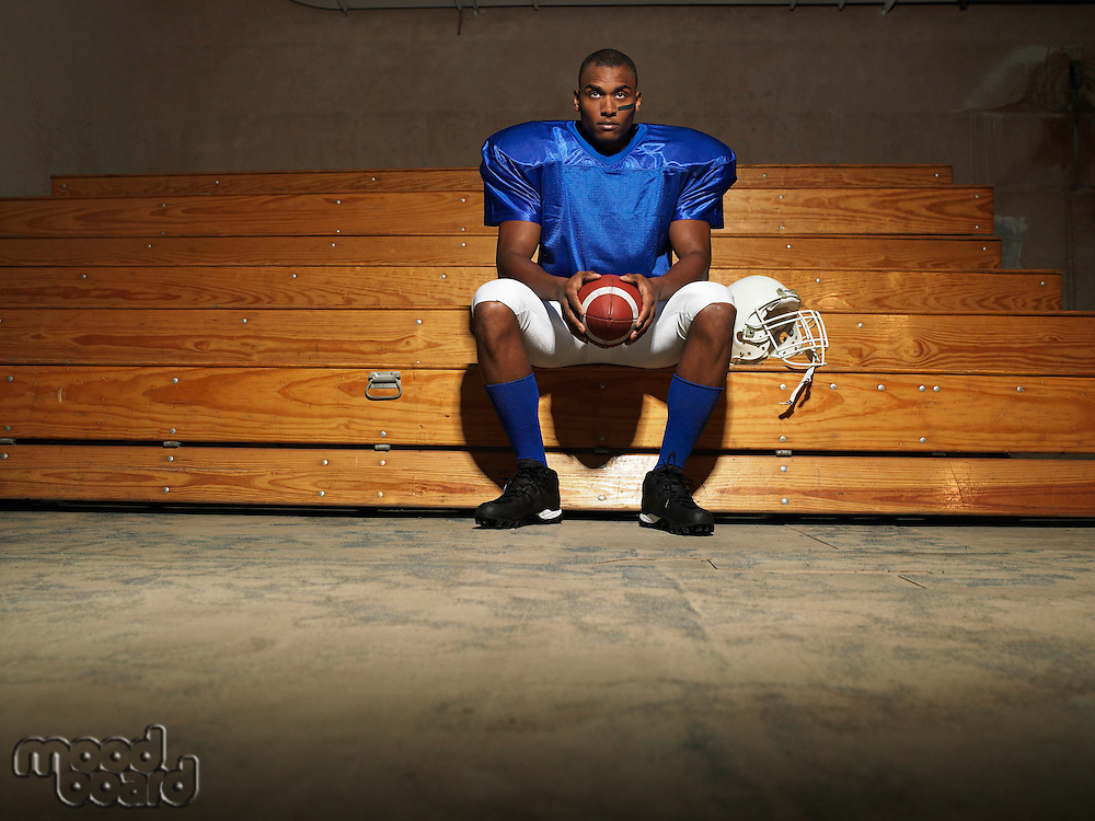 American football player sitting on bench holding ball portrait
