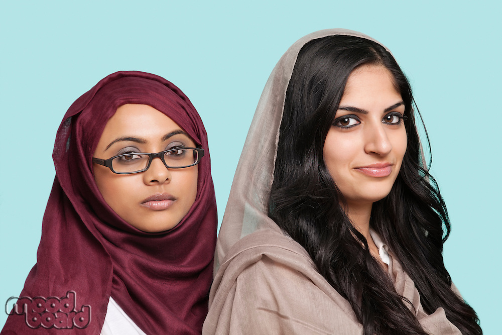 Portrait of two young Muslim women in traditional clothing against blue background