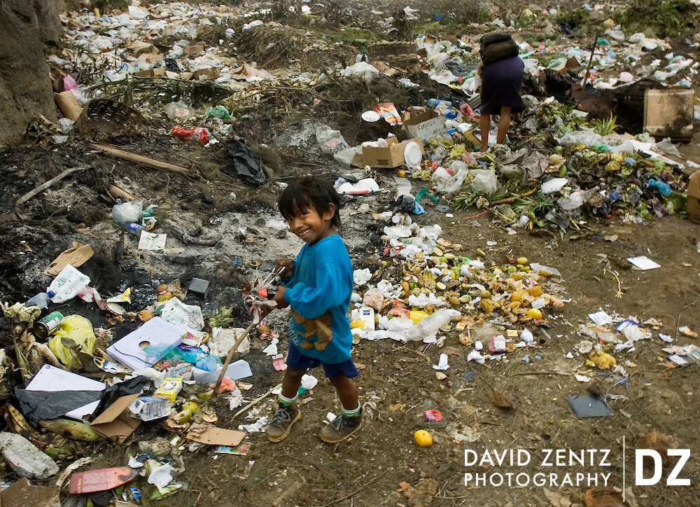 A boy stands amongst piles of garbage as his mother searches through the community dump for food and valuables in Jinotepe, Nicaragua on October 3, 2004. Nicaragua is the second poorest country in the western hemisphere.