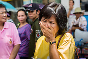 05 MAY 2013 - BANGKOK, THAILAND:   A woman weeps after waiting to see Bhumibol Adulyadej, the King of Thailand, in his royal motorcade Sunday. The King and Queen, who are both hospitalized and in poor health, did not attend Sunday's event. May 5 marks the 63rd anniversary of the Coronation of His Majesty King Bhumibol Adulyadej. The day is celebrated as a national holiday; since this year it falls on a Sunday, it will be observed on Monday May 6, and as such all government offices and commercial banks will close for the day. HM King Bhumibol Adulyadej is the longest reigning monarch in the world. Each year on the 5th of May, the Kingdom of Thailand commemorates the day when, in 1950, the Coronation Ceremony was held for His Majesty King Bhumibol Adulyadej, the 9th in the Chakri Dynasty (Rama IX). On the 5th of May, His Majesty conducts a merit making ceremony, presenting offerings to Buddhist monks, and leads a ?Wien Thien? ceremony, walking three times around sacred grounds at the Temple of the Emerald Buddha.    PHOTO BY JACK KURTZ