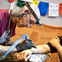 Manchester, UK - 4 August 2012: an artist creates a new tattoo to a visitor during the Manchester Tattoo Show, one of the most popular conventions of the UK tattoo community.