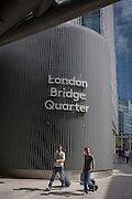 Two pedestrians pull their baggage beneath the modernity of London Bridge Quarter, Southwark, south London.