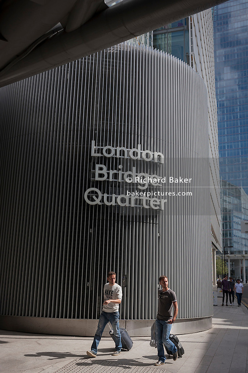 Two pedestrians pull their baggage beneath the modernity of London Bridge Quarter, Southwark, south London.