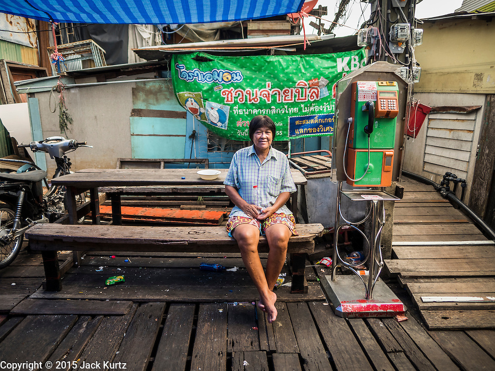 22 JULY 2015 - BANGKOK, THAILAND:    A woman at a table in a working class community on the Chao Phraya River south of Krung Thon Bridge. This is one of the first parts of the riverbank that is scheduled to be redeveloped. The communities along the river don't know what's going to happen when the redevelopment starts. The Chao Phraya promenade is development project of parks, walkways and recreational areas on the Chao Phraya River between Pin Klao and Phra Nang Klao Bridges. The 14 kilometer long promenade will cost approximately 14 billion Baht (407 million US Dollars). The project involves the forced eviction of more than 200 communities of people who live along the river, a dozen riverfront  temples, several schools, and privately-owned piers on both sides of the Chao Phraya River. Construction is scheduled on the project is scheduled to start in early 2016. There has been very little public input on the planned redevelopment.           PHOTO BY JACK KURTZ