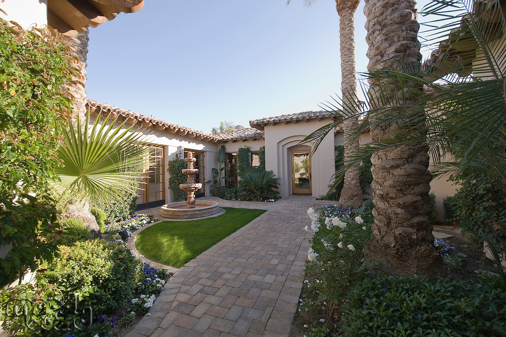 Paved path and water fountain in Palm Springs garden exterior