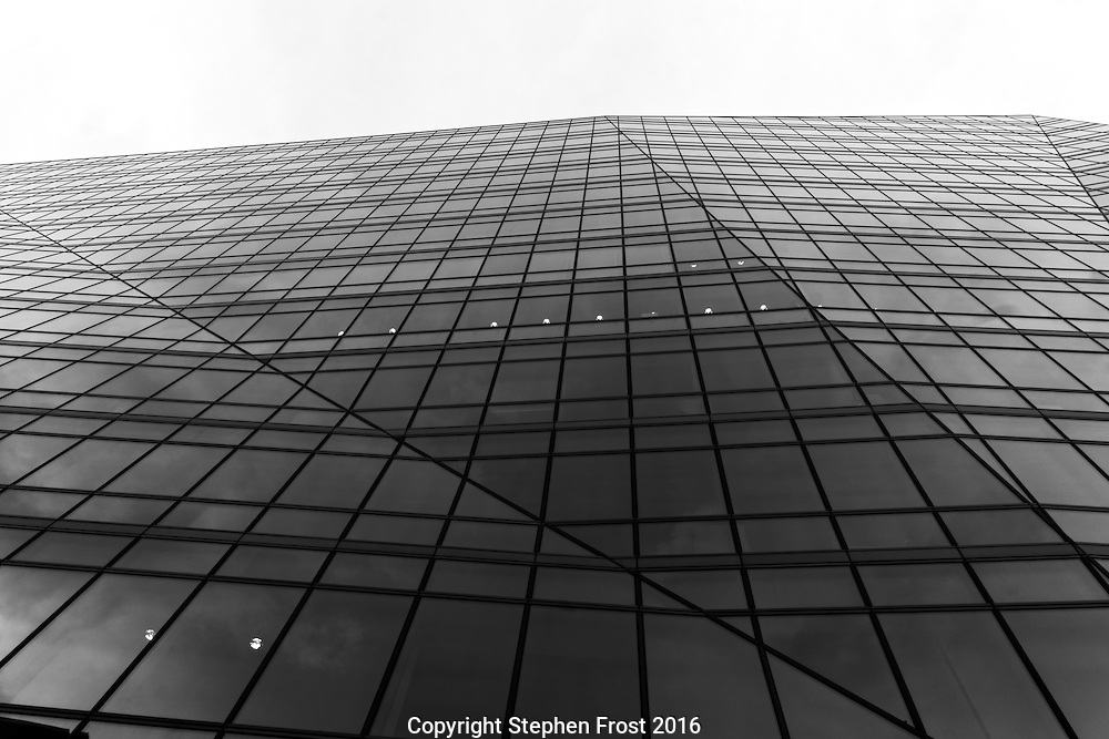 Abstract patterns made by the glass surface and edge of a modern office block.<br /> Photographed in London, England.