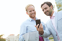 Businessmen using mobile phone against clear sky