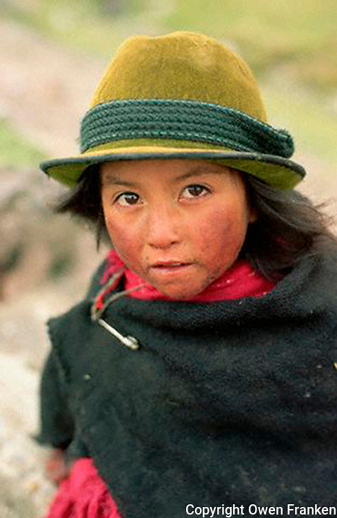 July 1995, Ecuador --- A little Ecuadorian girl wears a green hat and poncho to protect against the cold. --- Image by © Owen Franken/CORBIS