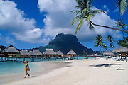 Bora Bora Lagoon Resort, Tahiti: woman walking on beach and bungalows on lagoon; Mount Pahia in distance..